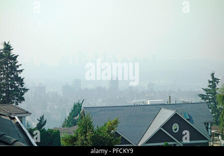 Burnaby, BC, Canada (Metro Vancouver). 21st August, 2018.  Looking south from North Burnab, the highrises in the distance are obscured by smoke coming from distant wildfires in the province. On this August morning air quality continues to be very poor and an advisory is in effect.  There are around 550 wildfires currently burning in British Columbia. Credit: Maria Janicki/Alamy Live News - Stock Image