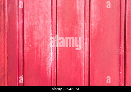 A wooden surface painted red with mild weathering, as a background image - Stock Image