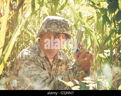 An army soldier man is holding a hand gun in the forest with tall grass outside for a defense, safety or combat - Stock Image