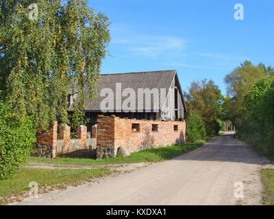 Repairing old shed with red brick walls - Stock Image