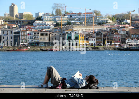 Young woman lying on the quay reading a book relaxing by the River Douro  with a view of the Vila Nova de Gaia in Porto Portugal Europe   KATHY DEWITT - Stock Image