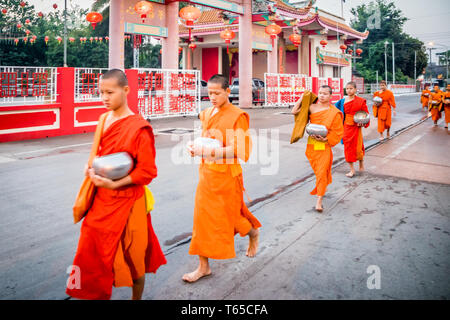 Mae Sot, Thailand - 3rd February 2019:   Young monks walking in a line past Chinese temple. Monks collect alms every morning. - Stock Image