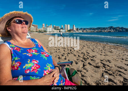 Benidorm, Costa Blanca, Spain, 28th November 2018. A Middle aged British tourist enjoys the winter sun on Poniente Beach in Benidorm as she escapes from the wet weather in the UK. Average temperatures over 17 degrees Celsius through the winter months make the Costa Blanca an ideal destination for cold and wet Brits. Credit: Mick Flynn/Alamy Live News - Stock Image