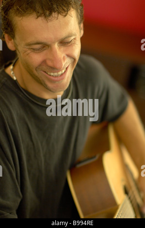 Young guy playing acousic guitar - Stock Image