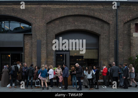 People queuing outside a busy restaurant (Dishoom King's Cross) in Granary Square, London, UK. - Stock Image