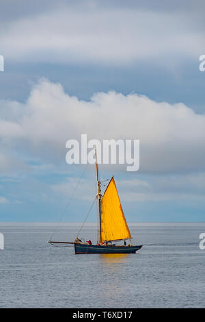 Mousehole, Cornwall, UK. 3rd May 2019. UK Weather. It was a cool start to the day, however the sunshine soon came out and brought a warm glow to the sail on this traditional boat which was weighing anchor off the coast at Mousehole early this morning. Credit Simon Maycock / Alamy Live News. - Stock Image
