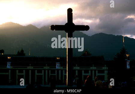 In the plaza by the cathedral in San Cristóbal de las Casas the Mayan Cross is illuminated by the sun setting - Stock Image