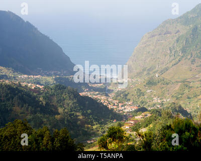View of a valley in Madeira island, Portugal, with the Atlantic Ocean in the background. - Stock Image