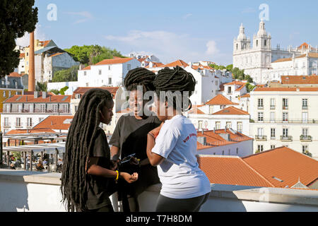 Group of girls young women with African hairstyles hair extensions talking together & view of Alfama district Lisbon Portugal Europe EU  KATHY DEWITT - Stock Image