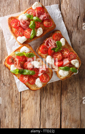 Delicious ciabatta with mozzarella, tomatoes, prosciutto and basil close-up on the table. Vertical top view from above - Stock Image