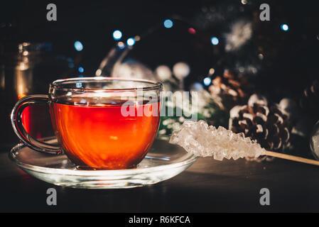 White sugar crystal near glass cup of hot tea; Winter still life; Postcard - Stock Image