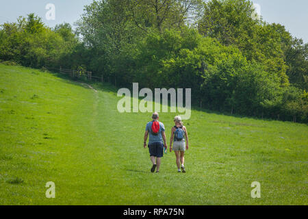 A couple in shorts with rucksacks follow the footpath up the hill from the village of Turville, Buckinghamshire - Stock Image