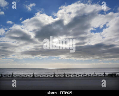 Cumulus clouds gather over the seafront on Hove Lawns promenade in the City of Brighton and Hove. - Stock Image
