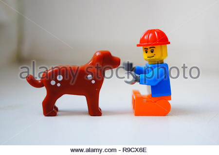 Poznan, Poland - December 22, 2018: Lego toy man having fun with his best dog friend in soft focus background.  - Stock Image