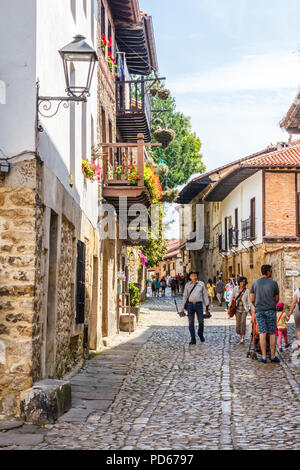 Santillana, Spain - 8th July 2018: Tourists walking up the street. The town has many historic buildings. - Stock Image