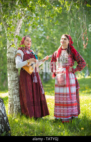 Two smiling woman in traditional russian clothes standing in the forest. One of them holding balalaika. Vertical shot - Stock Image