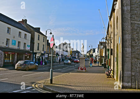 Street view of High Street Cowbridge from outside the old Town Hall building with the war memorial statue of a soldier to the front. - Stock Image