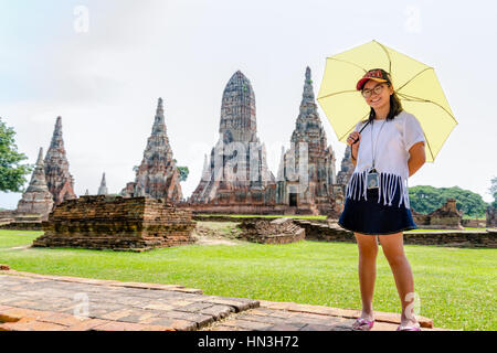 Tourist cute teenage girl wearing glasses with a camera neck, looking and smiled happily holding the umbrella on - Stock Image