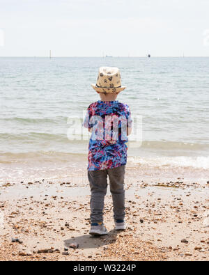 A boy in summer clothing looking out to sea at a beach - Stock Image