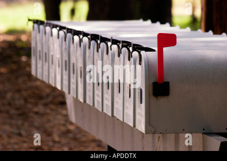 Long row of metal mailboxes with one red flag raised - Stock Image