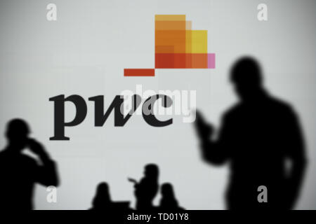 The PWC logo is seen on an LED screen in the background while a silhouetted person uses a smartphone in the foreground (Editorial use only) - Stock Image