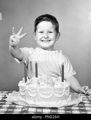 1950s PROUD SMILING BOY LOOKING AT CAMERA WITH BIRTHDAY CAKE HOLDING UP THREE FINGERS FOR HIS AGE - j6179 HAR001 HARS B&W EYE CONTACT CELEBRATE HAPPINESS HIS EXCITEMENT OCCASION UP SMILES JOYFUL GROWTH JUVENILES BLACK AND WHITE CAUCASIAN ETHNICITY HAR001 OLD FASHIONED - Stock Image