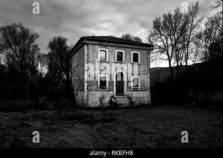 Detached and abandoned house illuminated by the light of the sunset - Stock Image
