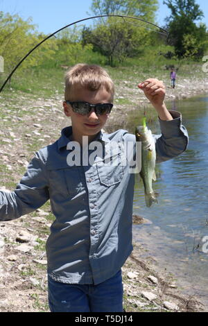 Boy proudly showing off the fish he caught - Stock Image