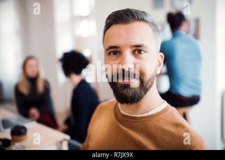 A portrait of young hipster businessman with colleagues in a modern office. - Stock Image