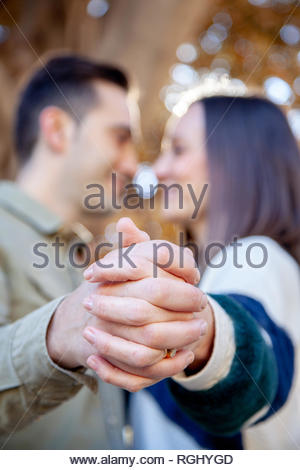 Young couple flirts in a public park with hands intertwined in the foreground in an European city - Stock Image