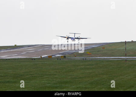 Leeds Bradford Airport, UK - 13 March 2019 Flight BE71 from Belfast landing in strong crosswinds at Leeds Bradford Airport this morning.  Flybe DH8D Bombardier Dash Credit: James Copeland/Alamy Live News - Stock Image