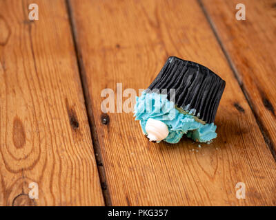 A cupcake with blue icing that has been dropped upside down onto a wooden floor - Stock Image