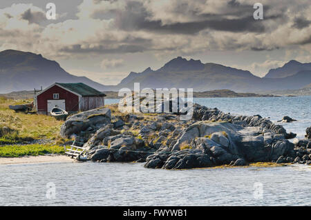 Boat house on the rocky shore of the North Atlantic near Hov on island Gimsøy on Lofoten in northern Norway. - Stock Image