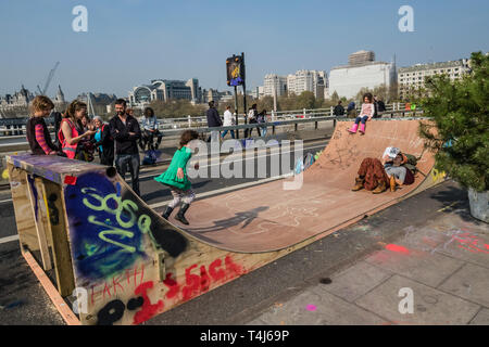 London, UK. 17th April 2019. TKids play on the skateboard ramp. wo days after Extinction Rebellion closed Waterloo Bridge turning it into a 'Garden Bridge' it remains closed to traffic despite a couple of hundred arrests. Activities continue on the bridge with new protesters arriving. Credit: Peter Marshall/Alamy Live News - Stock Image