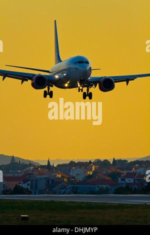 Landing civil passenger airliner in sunset against sky warm - Stock Image