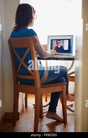 Young woman sitting at table, using laptop, on video call with mature woman, rear view - Stock Image