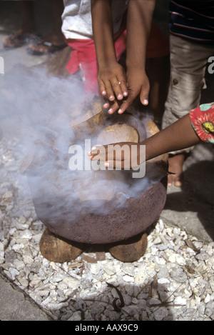 Childrens hands over copra cauldron - Stock Image