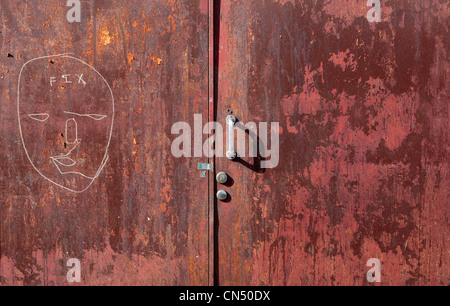 Red door and handle with peeling paint and face drawn in white pen with the word fix - Stock Image