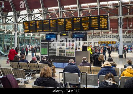 Travellers waiting by the illuminated display board at Paddington Station, london - Stock Image