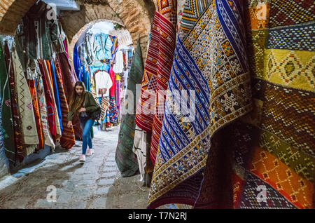 Chefchaouen, Morocco : A young woman walks under an arch past handwoven carpets for sale in the medina old town. - Stock Image