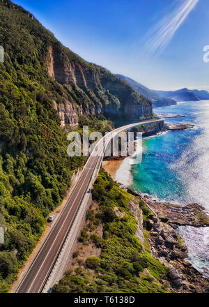 Grand Pacific drive segment of Sea Cliff Bridge passing around steep sandstone cliffs over waves of Pacific ocean on a sunny day in vertical panorama. - Stock Image