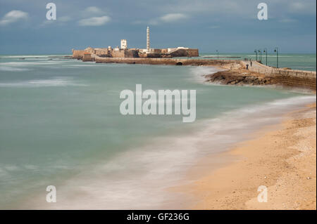 The Castillo de San Sebastian fortress and lighthouse, by the Caleta beach in the old town of Cádiz (long exposure) - Stock Image