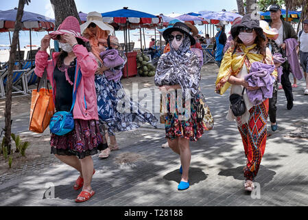 Women wearing face masks, shawls and hats to protect against the hot sun. Pattaya, Thailand, Southeast Asia - Stock Image