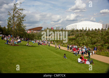 People sitting on lawns in sunshine on a sunny day with Velodrome and Basketball Arena at Olympic Park, London 2012 - Stock Image