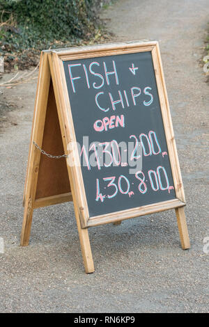 Opening hours A-Frame sign outside a Fsh and Chip shop in Cornwall. - Stock Image