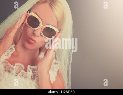 A young bride is dressed in a vintage style dress with classic classes in the studio for a marriage wedding or style - Stock Image