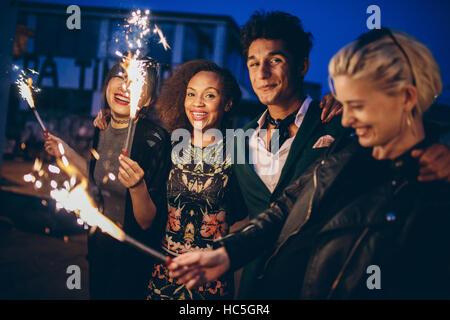 Shot of young friends at night with fireworks enjoying party. Group of friends with sparklers on road in evening. - Stock Image