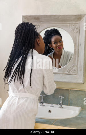 Pretty young african american woman doing her morning routine in front of the bathroom mirror - Stock Image