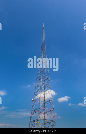 An old TV broadcast tower, against a blue sky. - Stock Image