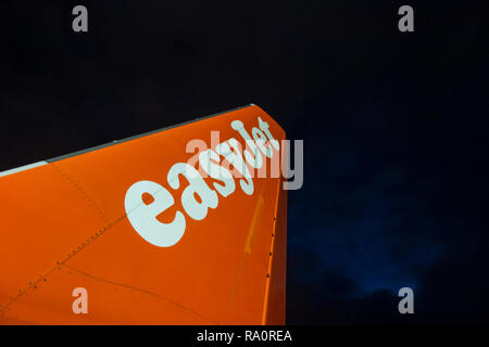 An Easyjet tailplane on the runway at night with a stormy sky above - Stock Image